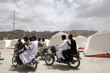 Motorcyclists pass by tents after an earthquake in Gosht