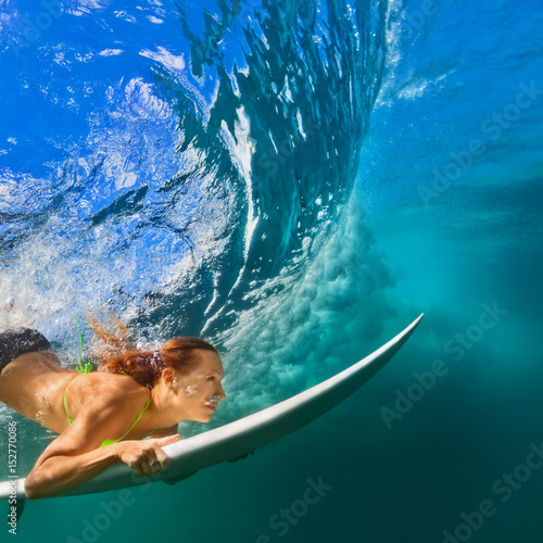 283ba614a2 Active girl in bikini in action. Surfer woman with surf board dive  underwater under breaking big wave. Healthy lifestyle. Water sport