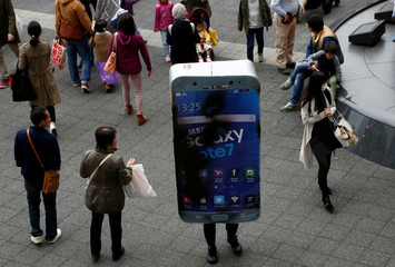 Participant wearing costume symbolising Samsung Galaxy Note 7 walks among pedestrians after a Halloween parade in Kawasaki