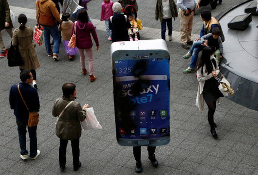 Participant wearing costume symbolising Samsung Galaxy Note 7 walks among pedestrians after a Halloween parade in Kawasaki