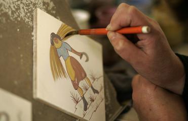 A woman paints a tile at Sant'Anna ceramic factory in Lisbon