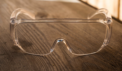 protective transparent plastic glasses on a wooden backgroun