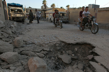 Men ride motorcycles near damaged ground due to an airstrike in the rebel held town of Sarmada, near the Syrian-Turkish border