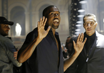 Rapper Kanye West reacts as he arrives to attend the Israeli-American designer Alber Elbaz Spring/Summer 2015 women's ready-to-wear collection for fashion house  Lanvin during Paris