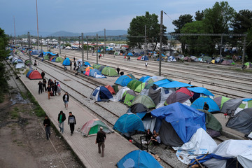 People walk past tents at a train station at a makeshift camp for migrants and refugees at the Greek-Macedonian border near the village of Idomeni