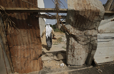 Palestinian man walks at his house which was damaged in an Israeli air strike in Gaza City