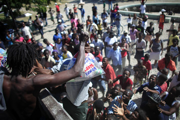A man holds a bag with food during a food distribution in front of the airport in Port-au-Prince