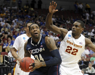 University of Connecticut's Oriakhi fights pressure from Iowa State University's Booker in their NCAA basketball game in Louisville