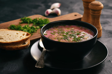 Homemade cold beetroot soup on black background.