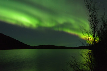 The Aurora in the sky above the hills and the lake.