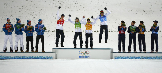 Germany's winning ski jumping team members jump on the podium during the flower ceremony for the men's team ski jumping final of the Sochi 2014 Winter Olympic Games