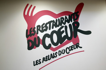 "The logo of the ""Les Restos du Coeur"" association is seen on a wall at a food distribution centre for the ""Les Restos du Coeur"" (Restaurants of the Heart) in Paris"
