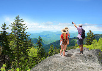 Family wearing backpacks hiking in summer mountains . Father and daughter on top of mountain taking photos of  mountains with phones. Close to Asheville, Blue Ridge Mountains. North Carolina, USA.