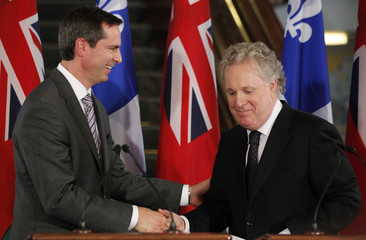 Quebec's Premier Charest and Ontario's Premier McGuinty shake hands during a news conference after a joint cabinet meeting in Quebec City