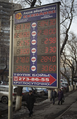 People walk past a board showing currency exchange rates in Almaty