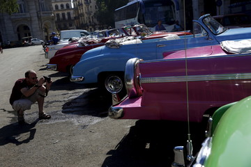 A tourist takes photographs of vintage cars in Havana
