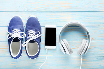 Sport shoes with smartphone and headphones on blue wooden table