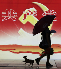 A woman and a pet dog walk past a poster depicting the logo of the Communist Party of China (CPC) in Chongqing municipality