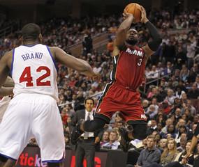 Miami Heat's Wade shoots past Philadelphia 76ers' Brand during NBA game in Philadelphia