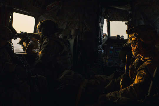 A crew member of a CH-47 Chinook helicopter mans a gun in front of a U.S. soldier while flying to an advising mission at an Afghan National Army headquarters for the 203rd Corps in the Paktia province of Afghanistan