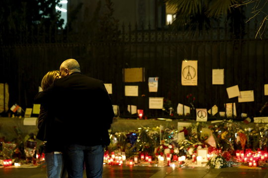 A man and a woman kiss and embrace as they stand next to candles and flowers in memory of victims of the deadly attacks in Paris outside the French embassy in Madrid