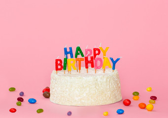 Happy birthday cake with color candles on pink background
