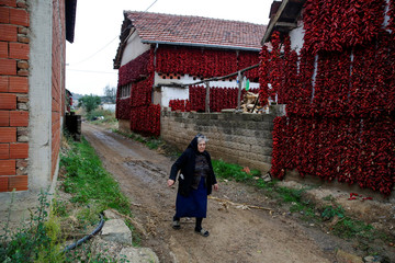 A woman walks along a road as bunches of paprika hang on the walls of houses to dry in the village of Donja Lakosnica