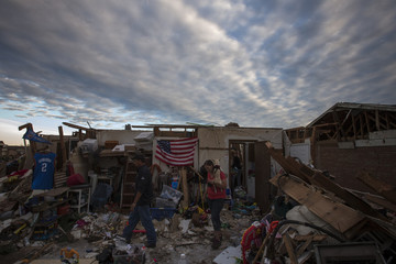 Residents walk through debris of homes after the suburb of Moore, Oklahoma was left devastated by a tornado