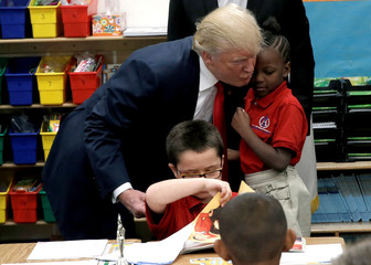 Republican presidential nominee Donald Trump hugs a student after receiving a bible as a gift during a campaign visit to the International Church of Las Vegas and the International Christian Academy in Las Vegas
