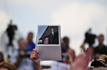 Supporter of Republican U.S. presidential candidate Romney holds photo during a campaign stop at Tom's Ice Cream Bowl in Zanesville