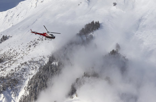 Scientists set up a laser measurement equipment before triggering an avalanche at the Vallee de la Sionne in Anzere