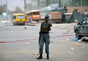 An Afghan policeman keeps watch at the site of bomb blasts in Kabul