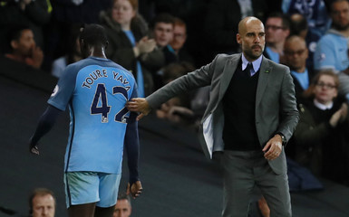 Manchester City's Yaya Toure with Manchester City manager Pep Guardiola after he is substituted