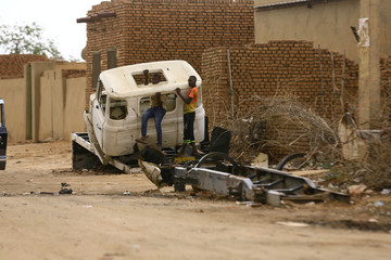 Boys are seen playing in an abandoned truck cabin in Al Fashir, capital of North Darfur