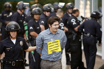 One of 21 protesters is arrested for trespassing during a protest outside the offices of Chase Bank in Los Angeles