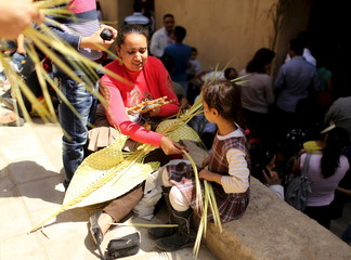 An Egyptian Coptic Christian woman makes palm decoration with her daughter during Palm Sunday inside a Church in Old Cairo