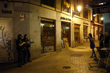 A woman confronts riot police as she takes photos of them during clashes after a protest against government austerity measures in central Madrid