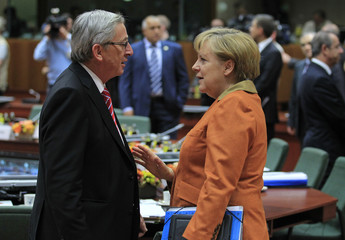 Luxembourg's Prime Minister Juncker talks with Germany's Chancellor Merkel during European Union leaders summit in Brussels