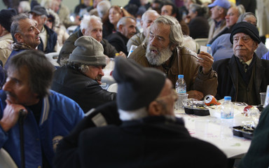 Homeless people sit at tables during a New Year's meal for the homeless in Athens