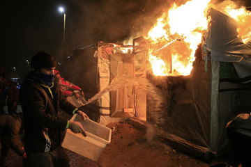 "Migrants attempt to extinguish flames from a burning makeshift shelter set ablaze in protest against the partial dismantlement of the camp for migrants called the ""jungle"", in Calais"
