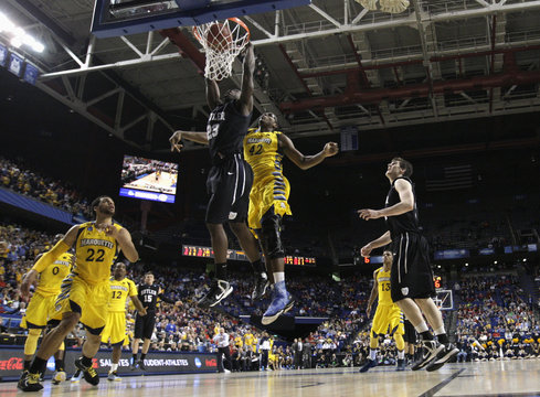 Butler University's Marshall fights to get his shot off under pressure from Marquette University's Otule during NCAA basketball game in Lexington