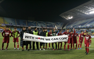 Japanese club Kashima Antlers players show a banner to their fans in Suwon