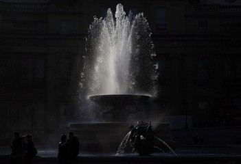 People stand by a fountain in Trafalgar Square in central London