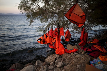 Lifejackets hang on a tree on a beach where refugees and migrants arrived on dinghies, with the coasts of Turkey seen in the background, on the Greek island of Lesbos