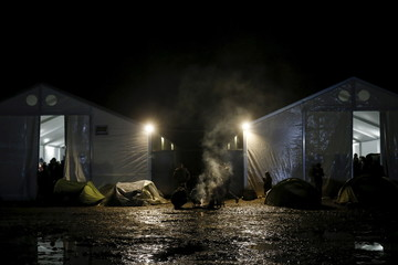 A bonfire smokes next to tents at a makeshift camp at the Greek-Macedonian border, near the village of Idomeni