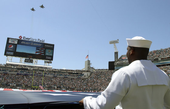 Sailor George Collins unfurl an American Flag before the start of the Tennessee Titans at Jacksonville Jaguars NFL game in Jacksonville