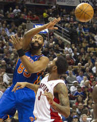 New York Knicks' Davis makes a blind pass over the head of Toronto Raptors' Forbes in their NBA basketball game in Toronto
