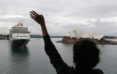 A spectator waves as the ocean liner Queen Elizabeth arrives in Sydney Harbour