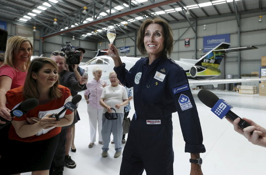 British aviator Tracey Curtis-Taylor celebrates with a glass of champagne upon her arrival at Sydney's International Airport in an open cockpit biplane