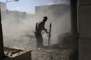 An anti-Gaddafi fighter reacts as an incoming RPG from Gaddafi forces explodes at a nearby street as they clash in Sirte